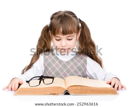 small schoolgirl reading big book. isolated on white background