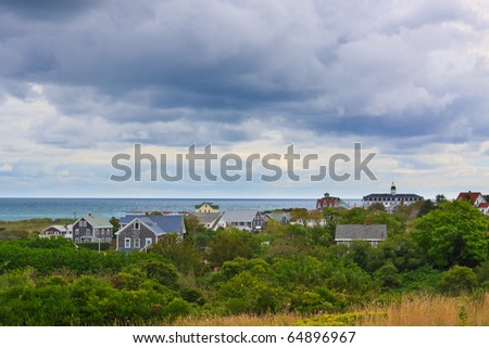 small seaside village on island with dramatic stormy sky - stock photo