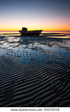 Small shipwreck stranded on the beach at sunset - stock photo