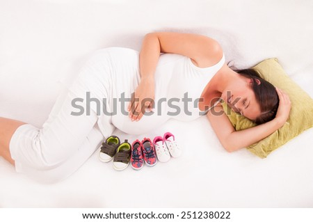 Small shoes for the unborn baby opposite the belly of pregnant woman - stock photo