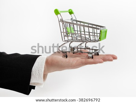 Small shopping trolley on the palm - stock photo