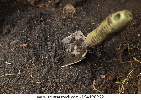 small shovel stuck in the soil - stock photo