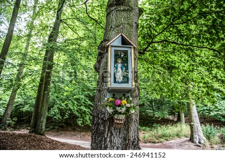 small shrine with Virgin Mary figure on tree in park in Gdansk, Poland