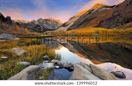 Small Sierra Nevada lake reflection spectacular fall color at dawn. - stock photo
