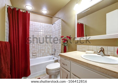 Small simple beige and red bathroom with white sink. - stock photo