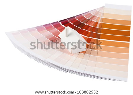 Small simple white model house on a color palette with different colors of red spectrum. - stock photo