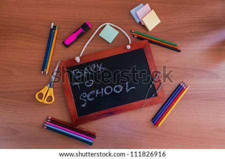 Small slate blackboard with the words Back to School surrounded by pencils, crayons, scissors and stationery - stock photo