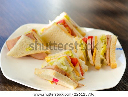 Small Slices of Tasty Sandwich with Ham and Veggies on White Plate, Served on the Wooden Table. - stock photo