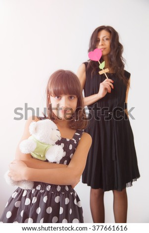 Small smiling child girl holding the teddy bear with her mother on background. Interior shooting, concept of family values, happy living, holidays celebration. - stock photo