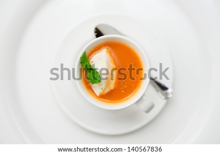Small snack - gazpacho soup served in coffee cup with whipped cream - stock photo