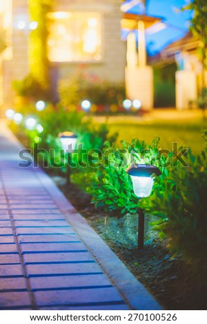 Small Solar Garden Light, Lanterns In Flower Bed. Garden Design. Solar Powered Lamp - stock photo