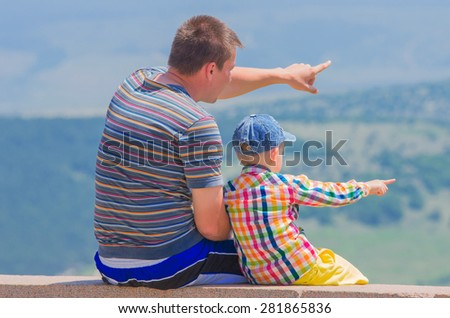 Small son and dad show each other something in the distance. Family composition