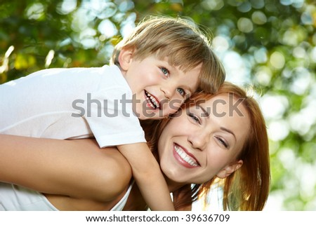 Small son piggyback on mother in a summer garden