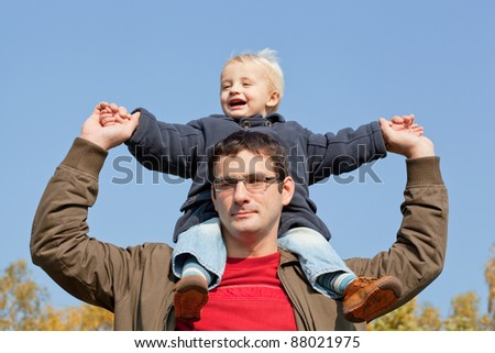 small son sits on shoulders at the father. Walk in autumn park in solar weather