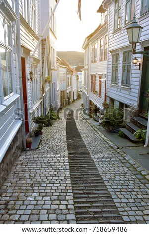 Small stone medieval street in the Bergen City, Norway. With the old wooden house on the side of the road. Old style. Typical stone road in norway.