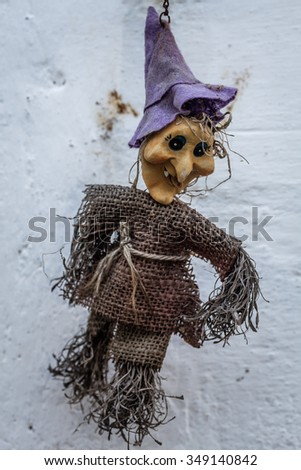 Small straw witch doll, hanging on the wall - stock photo