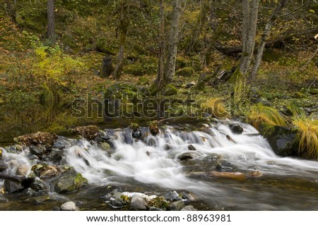 Small stream over rocky dam in autumn - stock photo