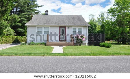 Small Suburban Bungalow Cottage Home Blooming Rhododendron Flowers Sunny Day - stock photo