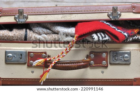 small suitcase filled ajar and warm clothing - stock photo