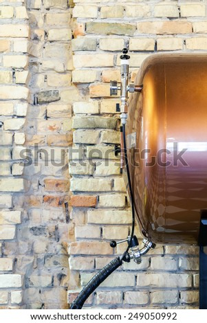 Small tank of beer next to brick wall - stock photo
