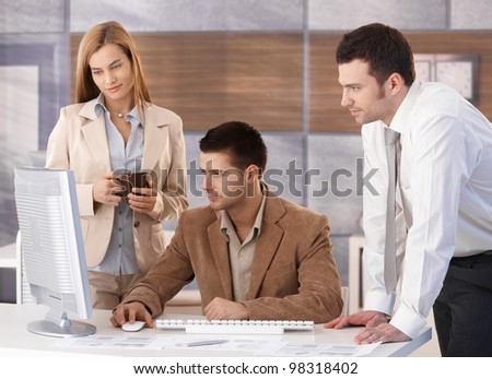 Small team of young businesspeople working together in office. - stock photo