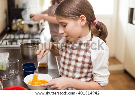 Small teenage girl in apron whisking eggs in white bowl in the kitchen - stock photo