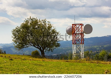Small telecommunication tower shot from the distance with mountains behind.