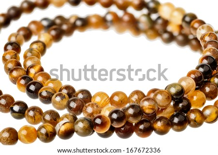 Small tiger eye beads on a string isolated on white - stock photo