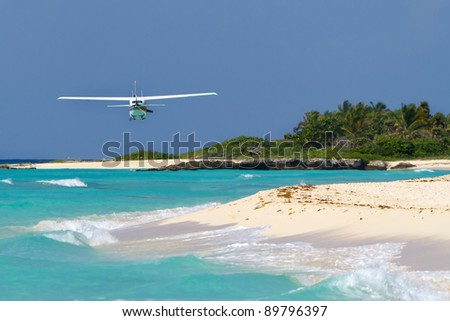 Small tourist plane over Caribbean beach in Mexico - stock photo