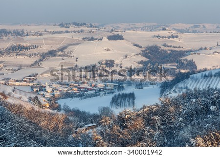 Small town among snowy hills in evening in Piedmont, Northern Italy. - stock photo