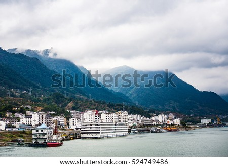 Small town at Yangtze river's edge with mountains and cloud background