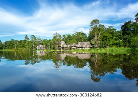 Small town in the Amazon rain forest reflected in the Yanayacu River near Iquitos, Peru - stock photo