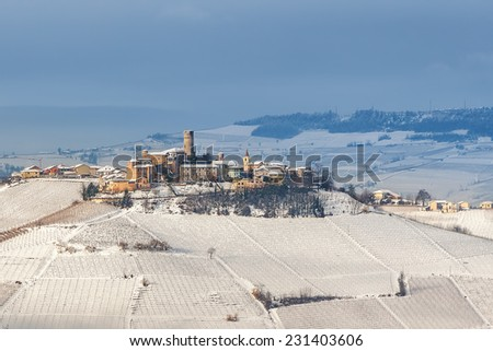 Small town of Castiglione Falletto on hill covered with snow in Piedmont, Northern Italy. - stock photo