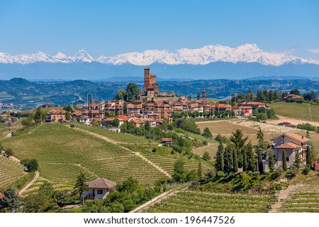Small town on the hill surrounded by green vineyards and mountains with snowy peaks on background in Piedmont, Northern Italy.