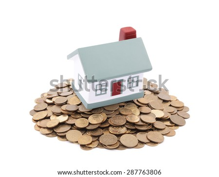 Small toy house on a pile of coins - stock photo