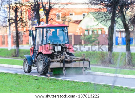 small tractor dust from sweeping the sidewalk in the summer - stock photo