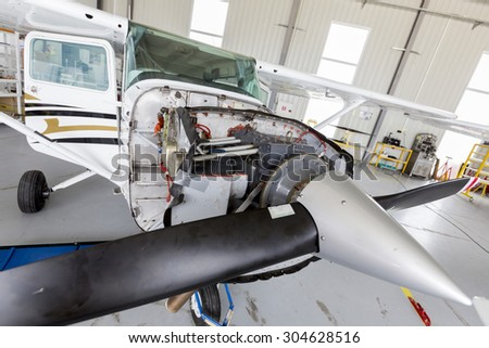Small two-seated propeller airplane is being repaired in a hangar at the airport.