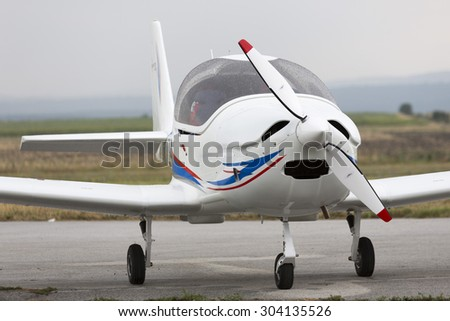 Small two-seated propeller airplane on the ground at the airport. - stock photo