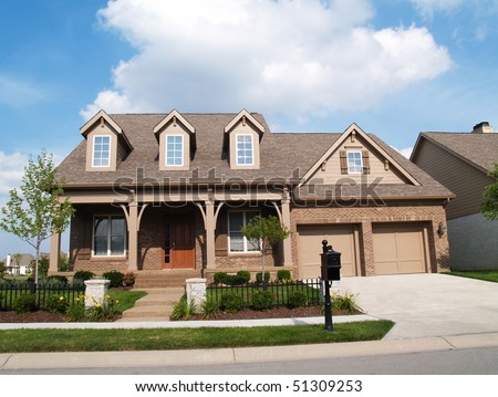 Small two story brick home with porch and a garage in front containing plenty of copy space, - stock photo