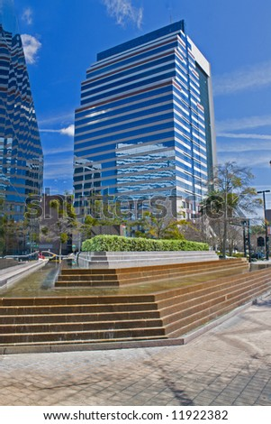 small urban park with fountain with skyscraper reflections - stock photo