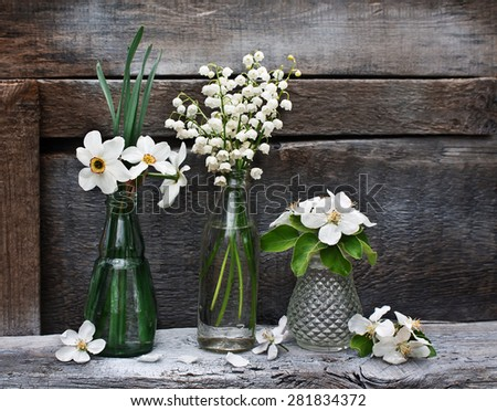 Small vases and bottles with spring flowers and flowering branches of apple on the old wooden background - stock photo