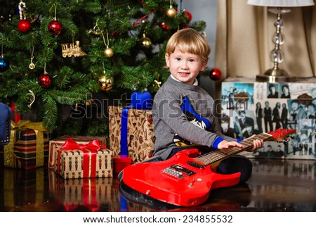 Small very cute blond boy holding red guitar on the background of the Christmas tree - stock photo
