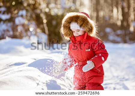 Small very cute girl in a red suit with fur hood plays with snow in winter on the background of the sunset forest - stock photo