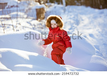 Small very cute girl in a red suit with fur hood winter amid the snowy forest - stock photo