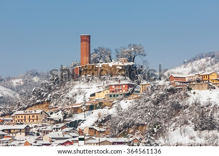Small village and old medieval tower on background covered with snow in Piedmont, Northern Italy. - stock photo