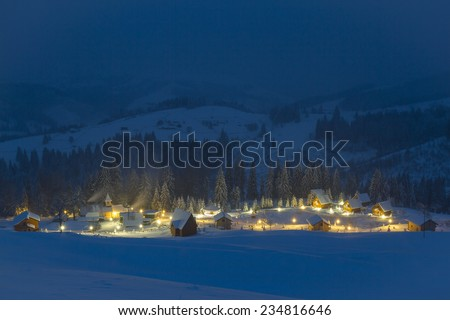 Small village in the snowy mountains in winter night - stock photo