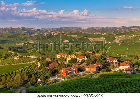 Small village surrounded by green vineyards at sunset in Piedmont, Northern Italy. - stock photo