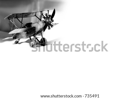 Small vintage metal barnstormer Bi-plane in black and white - represents aviation and travel. - stock photo