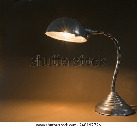 Small vintage metal lamp with flexible stand - stock photo