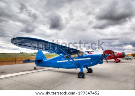 Small vintage single propeller airplanes parked on an airport tarmac. - stock photo